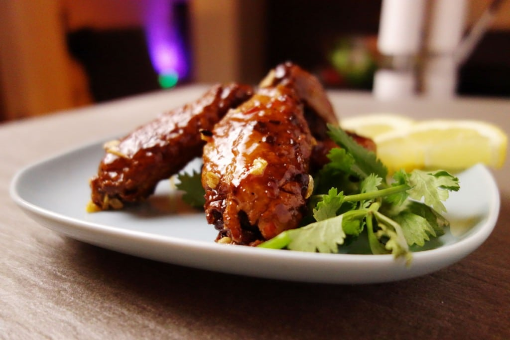 Vietnamese Wings served on a plate garnished with coriander and lemon