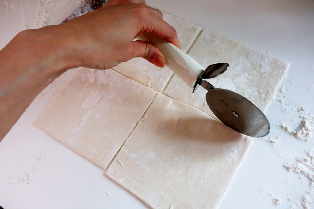 cutting the puff pastry into four with pizza cutter