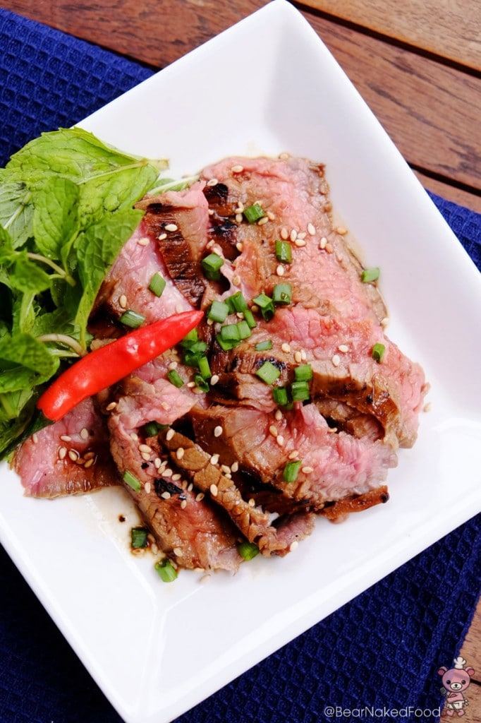 asian grilled flank steak garnish with mint leaves and spring onions