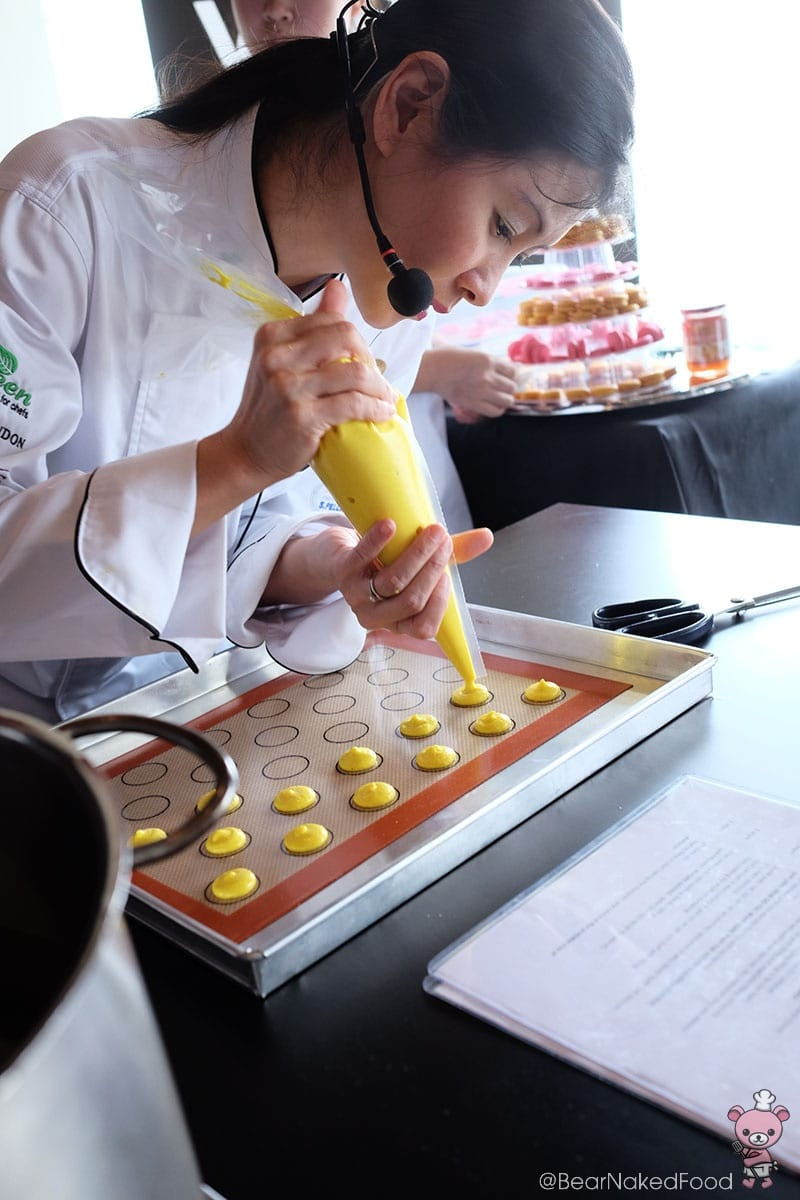Chef Michele Ow carefully piped the macaronage onto the silpat.