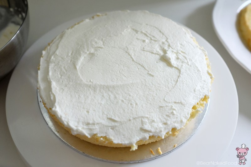 Spread a generous layer of whipped cream on one layer of the cake.